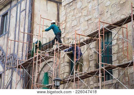 Workers With No Protection Belt Fixed On Scaffold At Construction Site