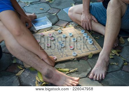 Closeup Two Old Men Playing Chinese Chess On Hanoi Sidewalk, Vietnam. Focus On Chessboard