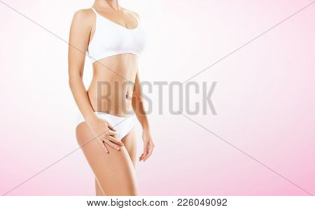 Fit And Sporty Girl In White Underwear. Beautiful And Healthy Woman Posing Over Magenta Background.