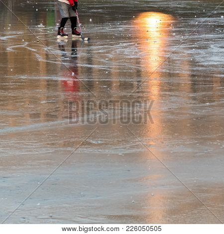 Ice Skater On A Frozen Pond With Reflection Sunbeams