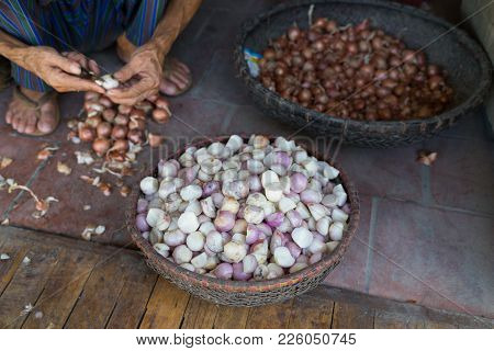 Basket Of Peeled Onions. Old Aged Man Hands Peeling The Onions On Floor