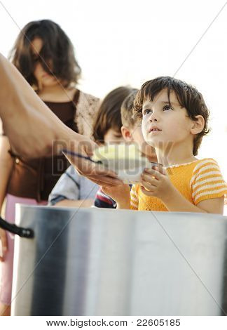 Hungry children in refugee camp, distribution of humanitarian food