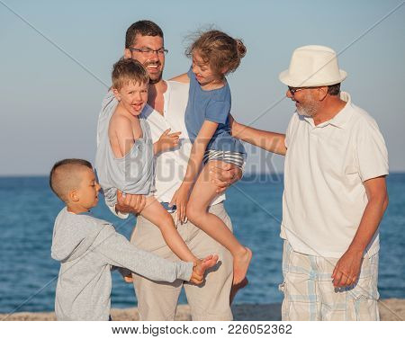 Group Of Five Family Members Different Generations - Three Kids, Two Boys And A Girl, Father And Eld
