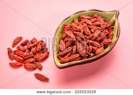 a small, leaf shaped bowl of dried red Tibetan goji berries (wolfberry) - superfruit