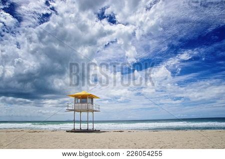 Beautiful View On The Beach And Lifeguard Tower Against Cloudy Blue Sky. Beach Safety Concept.