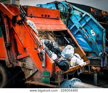 Back Of Old Garbage Truck With Waste. Urban Waste Management Concept.