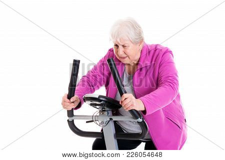 Female Senior With Thumb Up Train With Fitness Machine