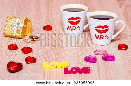 Lesbian Marriage Concept. Two Cups Of Coffee, Golden Gift Box With Marriage Rings And Hearts