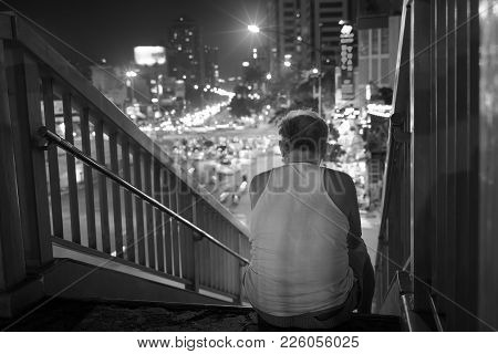 Old Man Sits On Walking Bridge Seeing Crowded City By Night. Concept Of Lonely Old Man