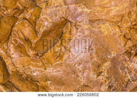 Background Of A Large Orange Crushed Stone. Torn Stone. The Surface Of The Cut Stone. Close Photogra