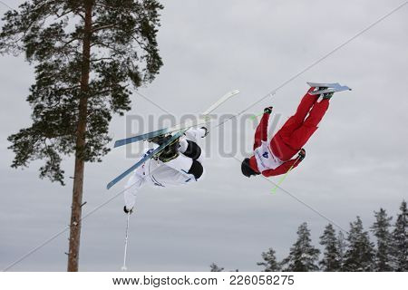KRASNOE OZERO, LENINGRAD REGION, RUSSIA - FEBRUARY 1, 2018: Albin Holmgren (white) of Sweden and Timur Rakhmatullin of Russia compete in dual mogul during Freestyle Europa Cup competitions