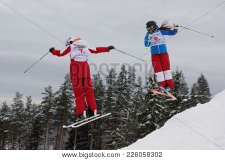 KRASNOE OZERO, LENINGRAD REGION, RUSSIA - FEBRUARY 1, 2018: Anastasiia Smirnova (red) and Yelizaveta Bezgodova, both of Russia, compete in dual mogul during Freestyle Europa Cup competitions