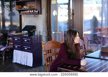 Model Waiting Photographer For Photoshoot In Cafe, Asian Smiling Girl Sitting Near Wooden Table. You