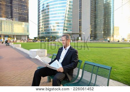Businessperson Reading Newspaper And Looking At Watch Outdoors In  . Concept Of Having Break, Restin