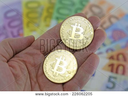 Hand With Two Big Goden Bitcoins And Blurred Euro Banknotes On The Background