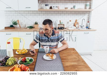 Man Eating Breakfast Using Smart Phone In Kitchen At Home