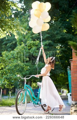 A Light Girl Near A Retro Bicycle Holds Up The Raised Helium Balloons In The Sun's Rays. Concept Of