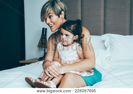 Curious Mother And Daughter Watching Tv In Bedroom. They Enjoying Cartoon And Sitting On Bed. Little
