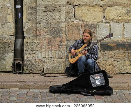 Riga, Latvia - April 29, 2017: Street Musician Is Playing Bass Guitar Outdoor In Riga, Latvia