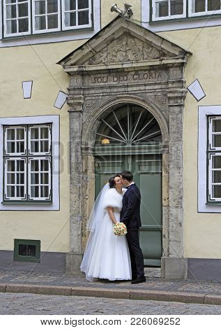 Fiance And Bride Are Kissing At The Entrance Of Building
