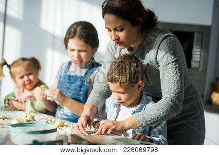 Mother Teaches Her Children How To Cook. Two Girls And The Boy Very Much Try. Their Faces In Flour,