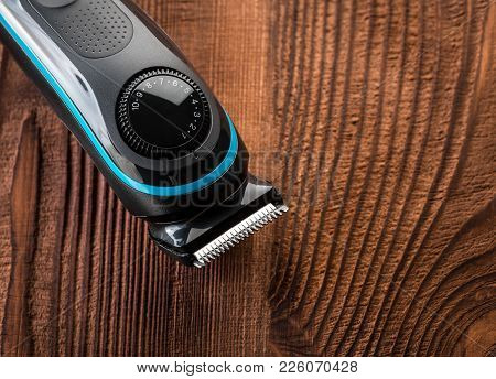Hair Trimmer And Scissors On The Wooden Background. Beard And Hair Clippers.