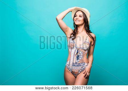 Full Length Happy Playful Slim Caucasian Female In Bikini And Wide Brim Summer Straw Hat Over Green