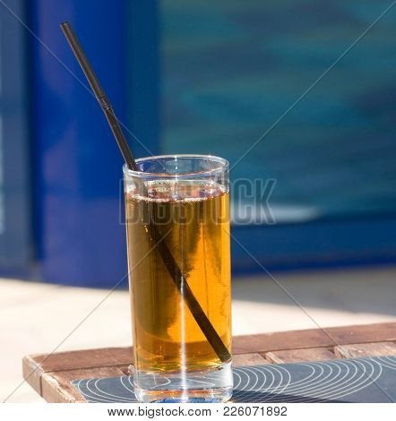 A Glass Of Fruit Juice And A Straw Is On The Table.
