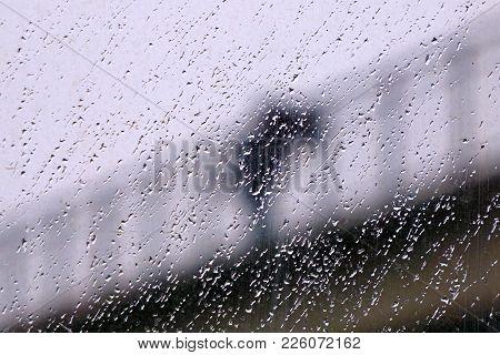 A Blurry Figure On A Bridge Suicide In The Rain. Rain Drops On Glass