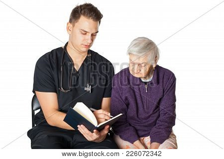 Old Disabled Woman With Young Male Carer Reading A Novel On Isolated Background