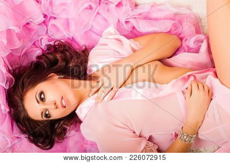 Young attractive woman lying on the pink cape