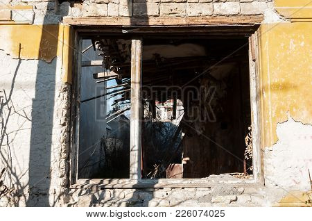 Windows And Remains Of Abandoned Damaged And Destroyed House By Grenade Shelling In The War Zone