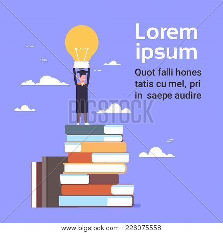 Happy Student In Graduation Cap And Gown Standing On Stack Of Books Hold Light Bulb On Blue Backgrou