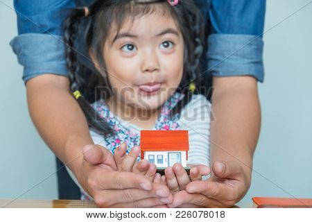 Father And Daughter Use Your Hand To Hold The House Model Together.