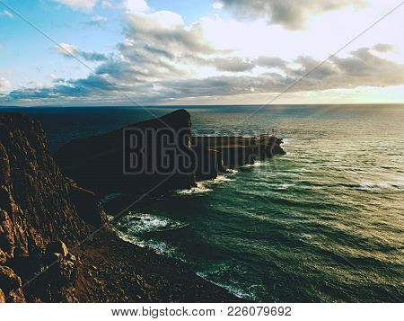 Neist Point Lighthouse On Rocky Cliff Above Wavy Sea. Blue Evening Sea And Sharp Cliffs, Isle Of Sky