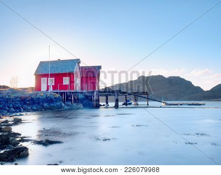 Norway Fishing Village On Stony Island. Shinning Red White Houses In Quiet Bay. Smooth Water Level M