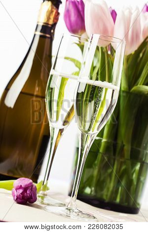 Two Glasses Of Champagne And Bouquet Of Tulips