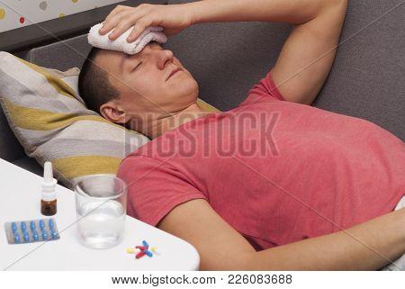 Man With Headache Lying On The Sofa