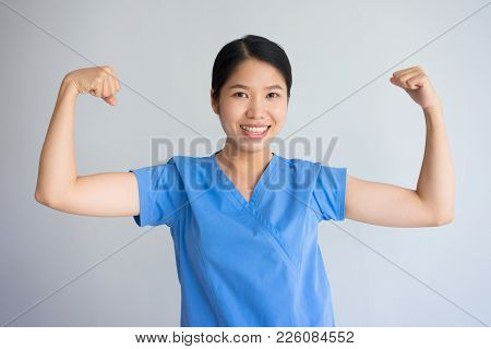 Smiling Asian Nurse Woman Showing Biceps At Camera. Metaphor Of Strength For Hard Health Care Work.