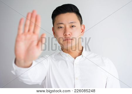 Strict Asian Businessman Raising Hand And Showing Stop Gesture With Palm. Young Serious Coach Warnin