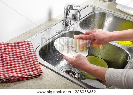 Hands Washing Dishes With Running Water From Faucet