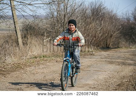 A Young Cyclist Is Driving Along The Country Road
