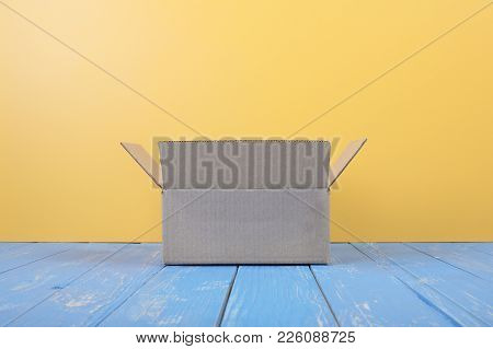 Postage And Packing Service - Open Package Front View On A Blue Wood And Yellow Wall Background.