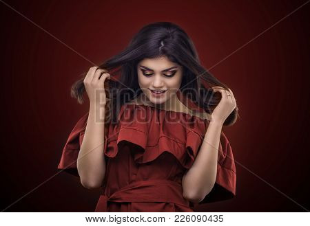 Brunette Woman With Long And Shiny Wavy Hair . Beautiful Model On Red Background. Studio Photosessio