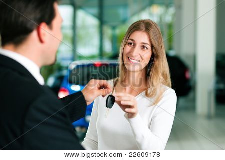 Woman at a car dealership buying an auto, the sales rep giving her the key