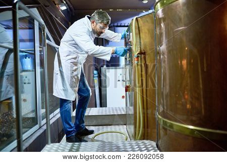 Serious Thoughtful Bearded Middle-aged Beer Engineer In Protective Eyewear Examining Brewery Equipme