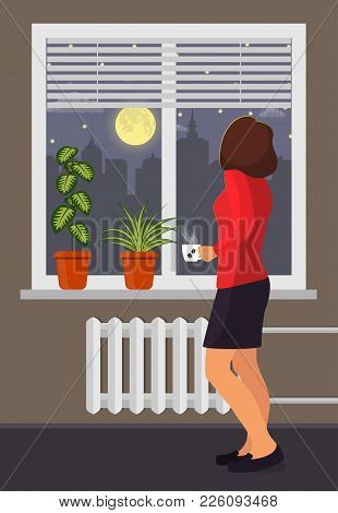 Woman With A Cup Of Coffee Stands By The Window. Room Plants In Pots On The Windowsill. Blinds On Th