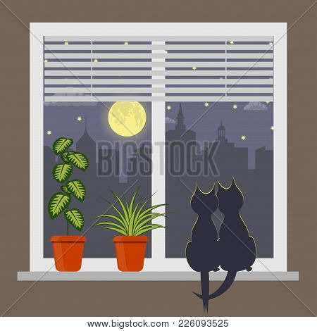 Silhouettes Of Two Cats Sitting On A Windowsill Under The Light Of The Moon. Night City Outside The