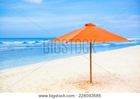 Bright Orange Parasol On The Sand Beach. Blue Sky And Sea In The Background. Orange Shadow Of Umbrel
