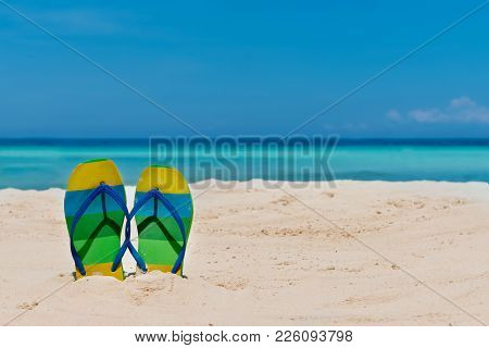 Sandal Flipflops On A Sandy Ocean Beach With Blue Sea And Blue Background With Copyspace. Tropical V